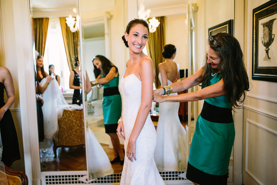 bride getting ready, putting on her dress at Villa Cortine Palace Hotel Sirmione