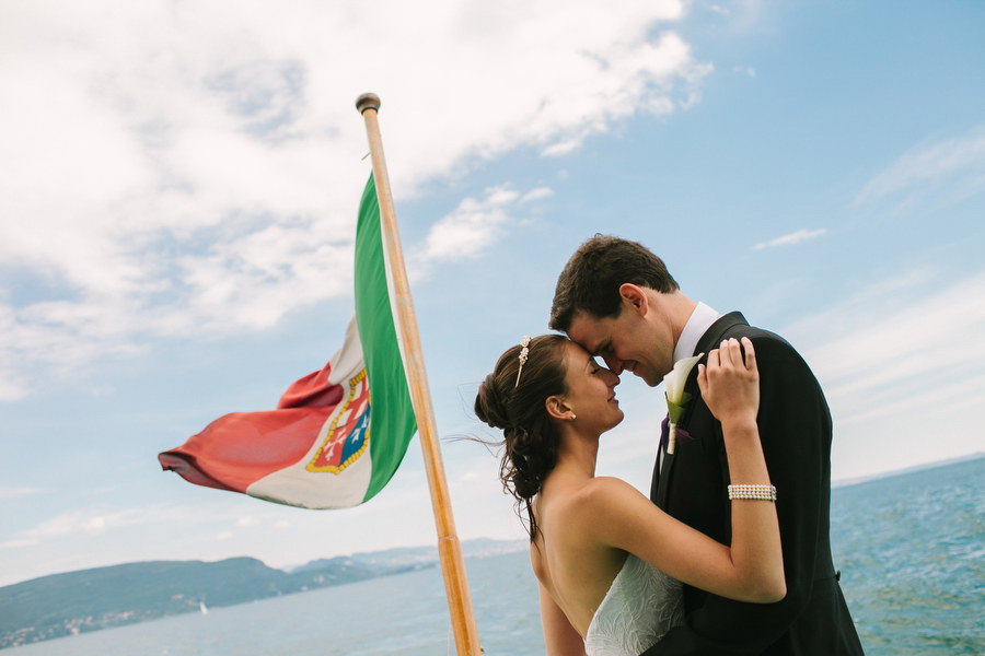 bride and groom portrait on a boat on lake garda, sirmione, italy